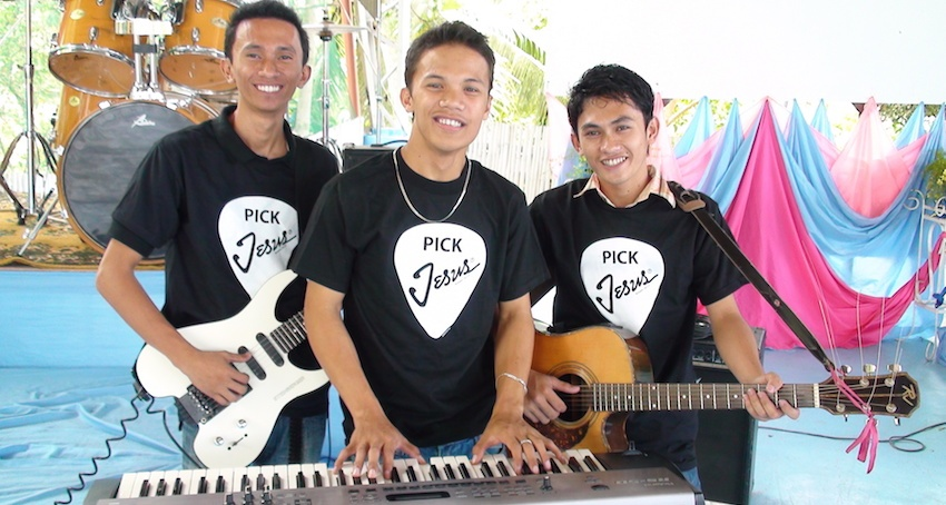 A worship team at a church in the mission field wears their Christian T-shirts proudly.