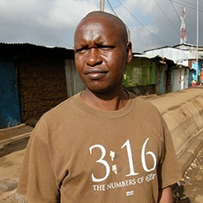 """Some missionaries serving in the slums of Nairobi, Africa, sent us a photo of a local resident they ran across, named Gus, short for Augustine. Gus was working in the slums, but nevertheless, he believed he has """"life in abundance,"""" and he was wearing a Kerusso shirt reading """"3:16 The Numbers of Hope!"""""""