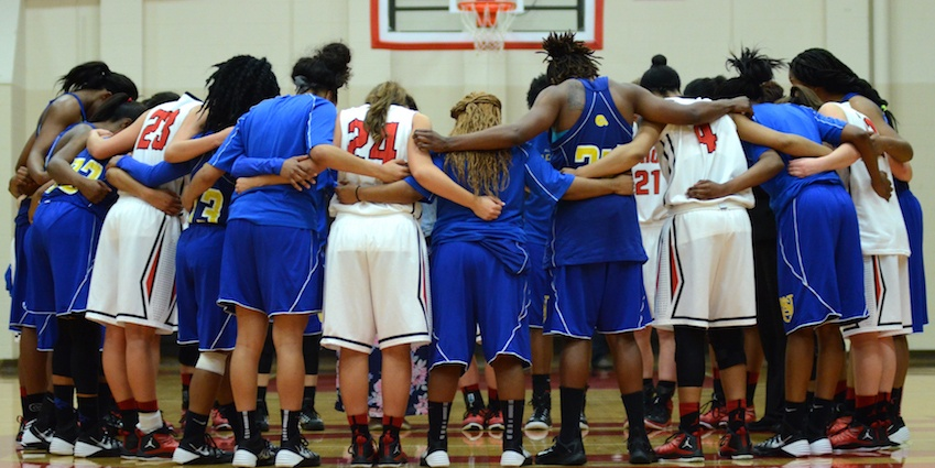 Union University's women's basketball team prays with an opposing team after a game. The college is located in Jackson, Tennessee.