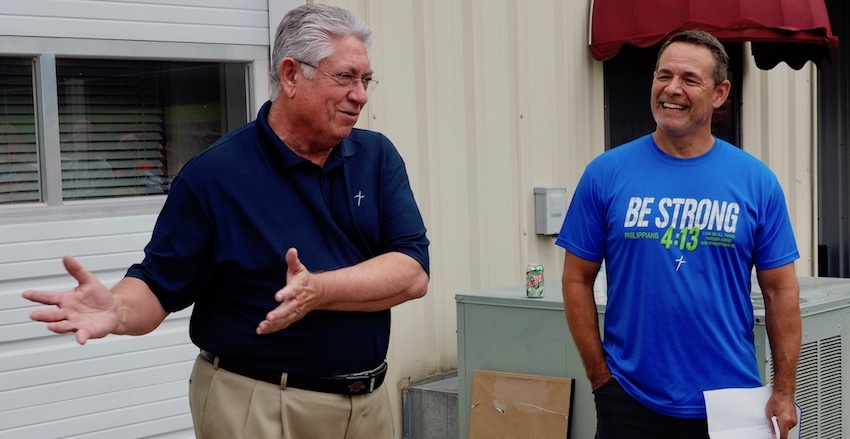 """Retiring HR Director Bob Ahart, left, describes his """"moment of glory"""" when, during his 30s, he returned an errant kick during a Dallas Cowboys scrimmage to """"make"""" the extra points, as Founder & CEO Vic Kennett laughs, during Ahart's retirement send-off party recently at Kerusso HQ. Ahart had been enjoying watching the scrimmage from the sidelines, with family who worked for Cowboys owner Jerry Jones."""